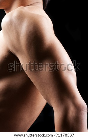 close up image of human muscular arm in front of black background - stock photo