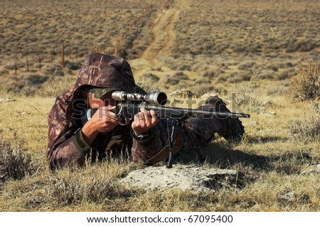 Close up image of male shooting rifle.  Image taken during big game hunting trip in Wyoming. - stock photo