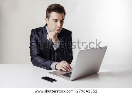 Close up image of multitasking business man using a laptop and mobile phone - stock photo