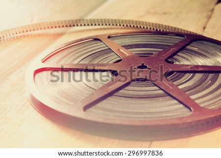 close up  image of old 8 mm movie reel over wooden background. retro style image  - stock photo
