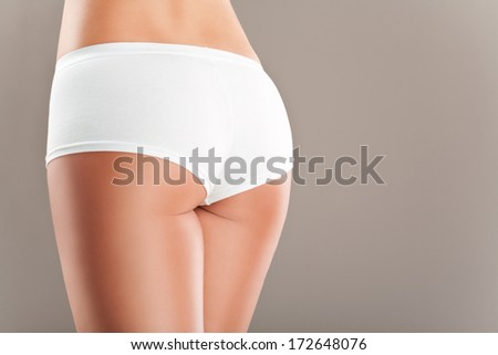 Close up image of perfect,smooth skinned,sexy female buttocks in white panties.Studio shot.Careful skin retouch - stock photo