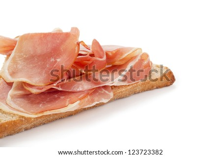 Close up image of Prosciutto ham in slice of bread against white background