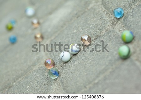 Close up image of scattered colorful marble on street - stock photo