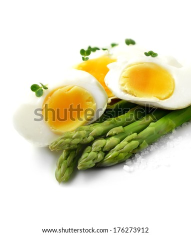 Close-up image of soft poached eggs with steamed asparagus stems and rock salt granules against a bright background. Perfect for your breakfast menu design or article on healthy eating. Copy space. - stock photo