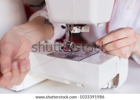 Close-up image of tailor sewing on sewing machine. Insert thread into the needle.