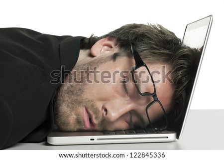 Close-up image of tired businessman sleeping on his laptop against the white surface