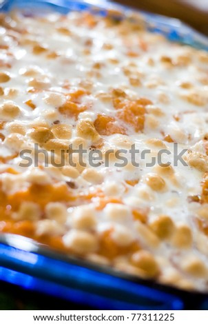 Close up image of traditional sweet potato casserole with browned marshmallow topping.
