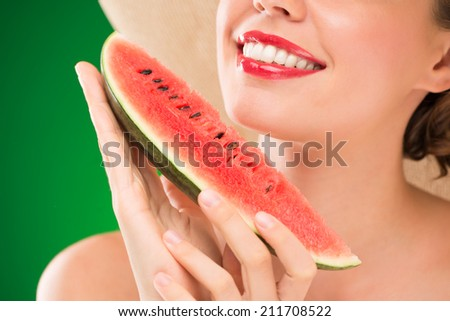 Close-up image of unrecognizable woman with red lips eating watermelon