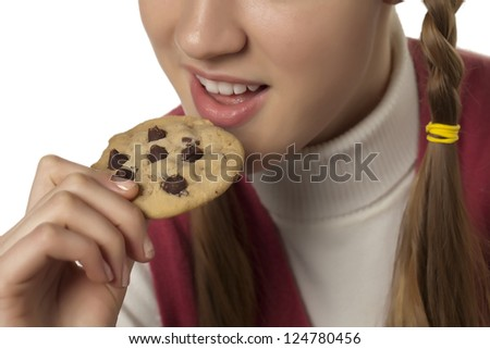Close up image of woman eating chocolate cookie against white background - stock photo