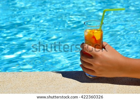Close up image of woman hand holding glass of cocktail in front of swimming pool
