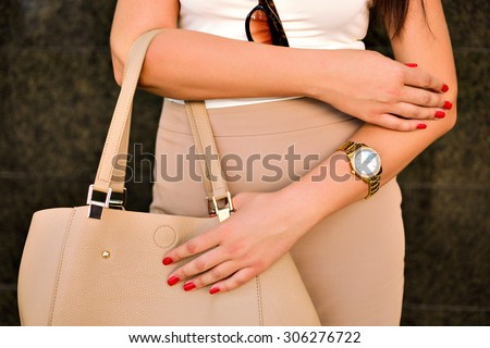 Close up image of woman hand, with stylish gold classic watches, fashion details, young businesswoman, beige golden colors. - stock photo