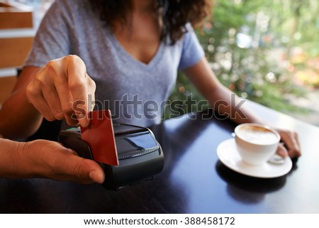 Close-up image of woman paying with credit card in cafe - stock photo