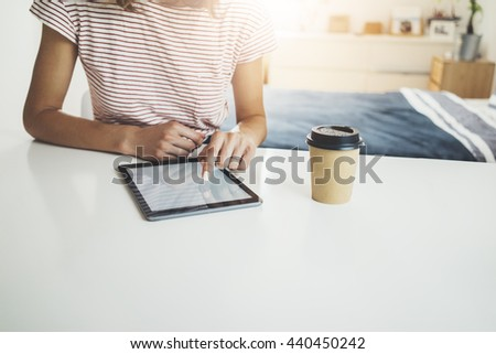 Close-up image of young hipster girl using digital tablet at home interior, female hands typing on touch screen of portable tablet, social networking concept, coffee to go on white table
