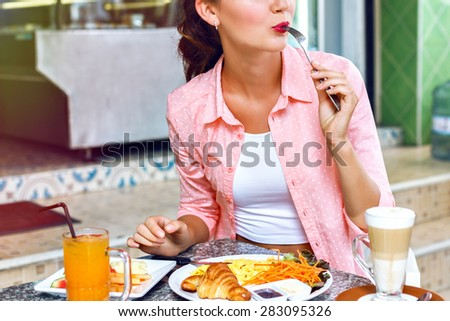 Close up image of young woman eating classic breakfast a tasty omelet, fresh croissants, coffee and fresh juice oranges. This energy boost for the whole day. - stock photo