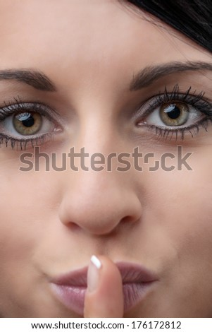 close up image of young woman with finger on her mouth to indicate that you should be quiet