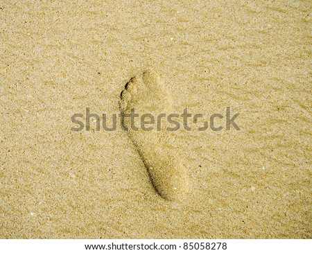 Close-up image with one footprint on the sand beach - stock photo