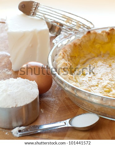 Close up in Kitchen of an Empty Quiche Pie Crust and the Ingredients.  The pie shell  was brushed with egg before baking and now ready for filling. - stock photo