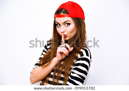 Close up indoor fashion lifestyle portrait of cool pretty young brunette girl, amazing long hairs, bright makeup, red hat and stripy t shirt, cute face, image with flash, say shhh, science . - stock photo