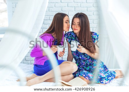 Close up indoor lifestyle portrait of two pretty cheerful girls holds cup of coffee . - stock photo