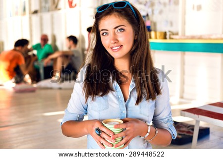 Close up indoor portrait of young pretty brunette woman, drinking morning coffer in cafe, fresh natural make up and long hairs, cute smile, fun, joy. - stock photo