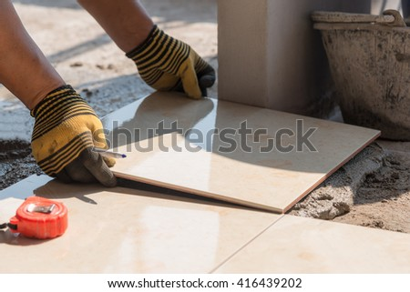 Close-up Installing tiles floor in construction work - stock photo