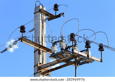 close-up insulator power lines against the blue sky  - stock photo