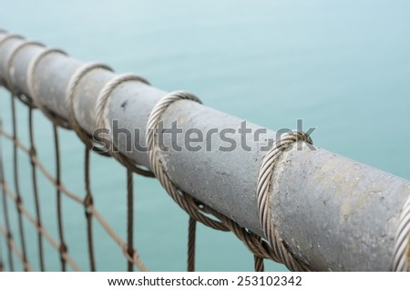 Close Up Iron Wire Fence, Background by the Sea. - stock photo
