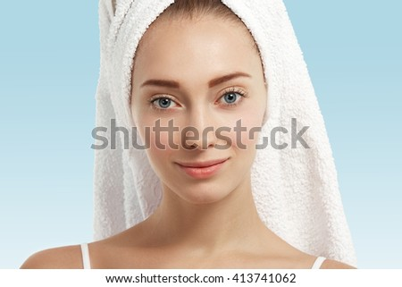 Close up isolated portrait of beautiful young Caucasian woman with blue eyes and healthy clean skin looking and smiling at the camera wearing white towel on her head against blue studio background.  - stock photo