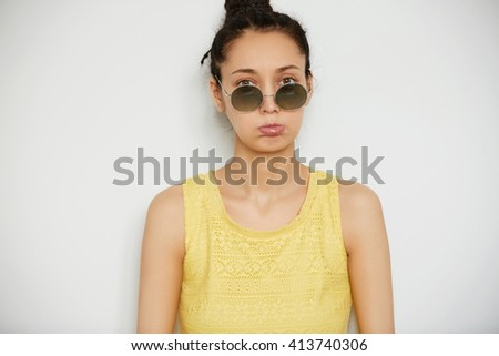 Close up isolated portrait of upset young dark-haired woman in sunglasses and stylish top looking at the camera with sad expression against white background. Human face expressions and emotions - stock photo