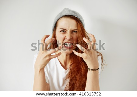 Close up isolated portrait of young annoyed angry woman holding hands in furious gesture. Young female with red hair in white T-shirt and cap. Negative human emotions, face expressions. Film effect  - stock photo