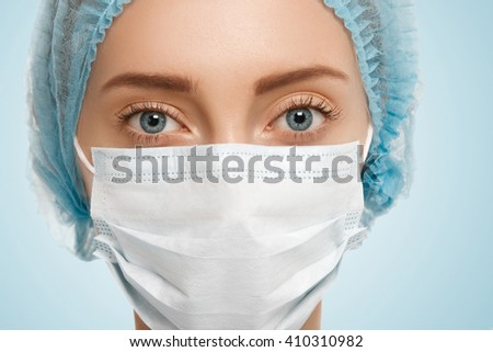 Close up isolated portrait of young Caucasian female surgeon wearing surgical mask and blue cap looking serious and confident at the camera against blank wall background. Plastic surgery concept    - stock photo