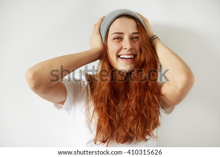 Close up isolated portrait of young redhead female with happy toothy smile posing against white background holding hands at her head, looking cheerfully at the camera. Body language. Film effect - stock photo