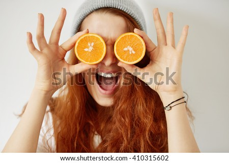 Close up isolated portrait of young redhead woman holding halved oranges at her eyes. Headshot of funny girl wearing white T-shirt and gray cap. Human face expressions and emotions. Selective focus - stock photo