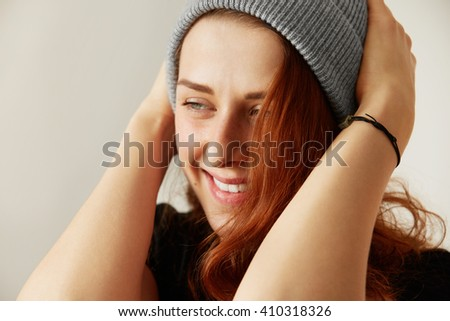 Close up isolated view of attractive smiling young girl with long loose red hair, wearing black T-shirt and cap, looking away, holding her head. Human face expressions and emotions. Selective focus - stock photo