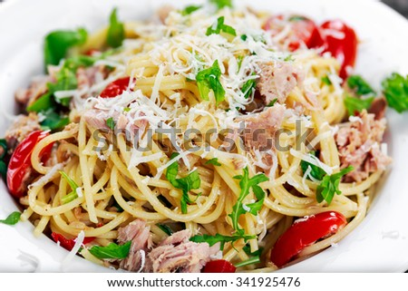 Close up Italian Tuna Pasta spaghetti with tomato, chili, parmesan cheese and wild rocket leaves. - stock photo