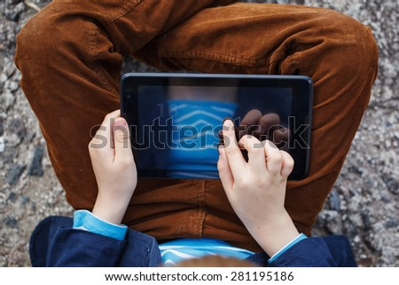 close up  kid's hands multitasking  using tablet, laptop for playing or education  - stock photo
