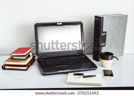 Close up Laptop Computer on Top of Office Table of a Businessman with Empty White Screen