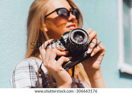 Close up lifestyle details,young hike hipster woman holding retro sunglasses,golden jewelry,warm colors.holding vintage retro camera on her hands,stylish classic accessorizes - stock photo