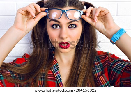 Close up lifestyle fashion portrait of young hipster teen girl with bright make up and two funny ponytails, surprised positive emotions. - stock photo