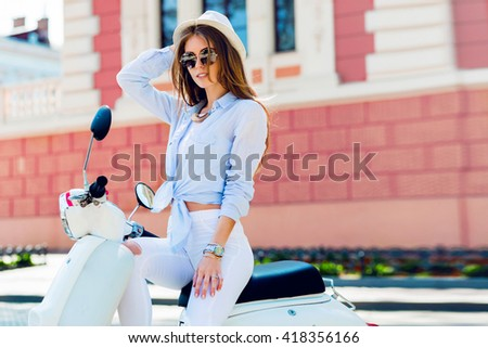 Close up lifestyle  image of young fashionable woman in casual outfit sitting on scooter   on the street.    Wearing blue shirt, white pants, trendy sunglasses. Tourist woman enjoying  holidays . - stock photo