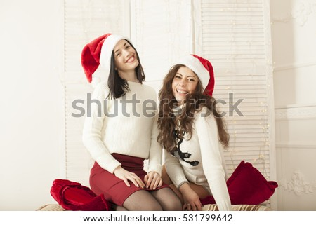 Close up lifestyle indoor portrait of two young woman posing near decorated Christmas