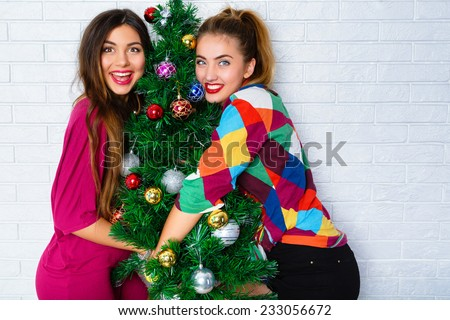 Close up lifestyle indoor portrait of two young woman posing near decorated Christmas tree, at New Year eve. Smiling having fun, ready for celebration. Bright holiday image of best friends. - stock photo