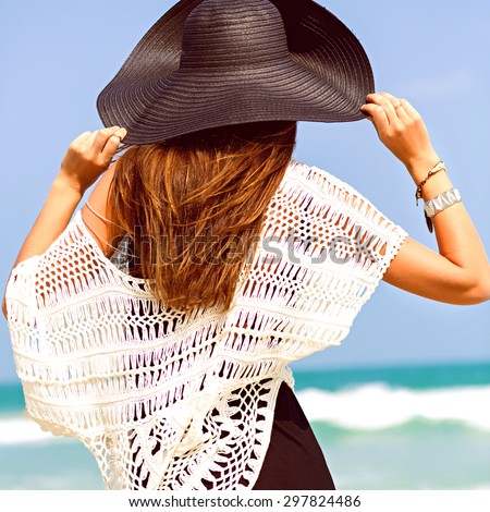 Close up lifestyle outdoor portrait of elegant stylish lady posing near ocean at tropical exotic country. Pretty model looking on clear blue sea, vacation, relax, travel. - stock photo