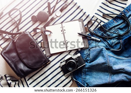 Close up lifestyle photo of hipster student accessories . Still life of random objects of modern girl / woman.  Leather bag, camera, Sunglasses, jacket, paper notepad, Aerial view. - stock photo