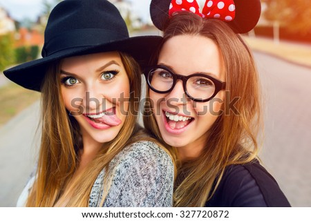 Close up lifestyle  portrait  of  girls best friends makes funny  grimaces on camera , show tongue  and laughing together.Two women posing outdoor, warm sunny evening colors. - stock photo