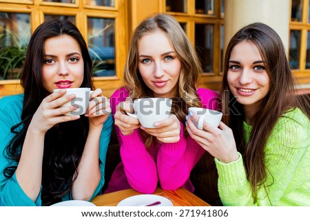 Close up lifestyle portrait of three beautiful  young  women sitting in caffe and enjoying  hot tee . Wearing bright neon yellow , pink and blue stylish  sweater .Holidays, food and tourism concept . - stock photo