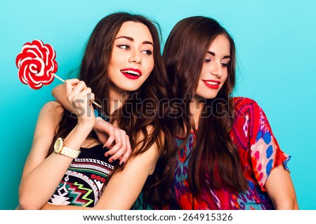 Close up  lifestyle portrait of two  attractive  fancy  friends  in  colorful hipster  fashionable   outfit .  Women  holding pink lolly pop and having fun together against blue wall. - stock photo