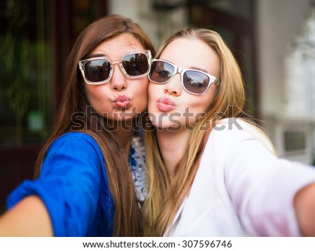 Close up lifestyle selfie portrait of two young positive woman having fun and making selfie, teenage hipster trendy clothes and sunglasses, long hairs,fresh make up. happy together. sisters, friends - stock photo
