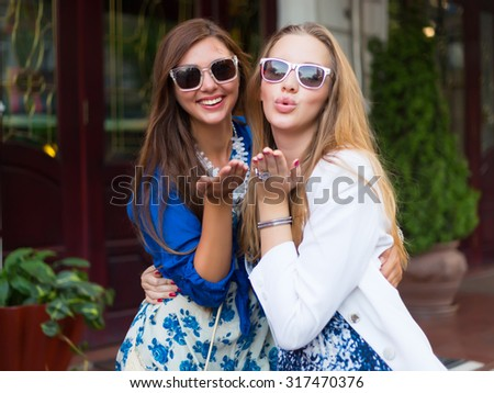 Close up lifestyle selfie portrait of two young positive woman having fun, teenage hipster trendy clothes and sunglasses, long hairs,fresh make up. happy together. sisters, friends.Sending kisses.   - stock photo