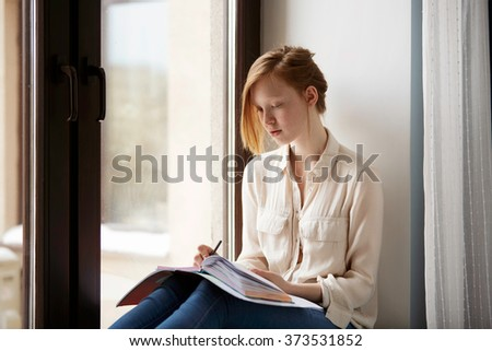 Close up lifestyle soft image of pretty young woman sitting on her window and making notes to her diary.  Fall season mood. - stock photo